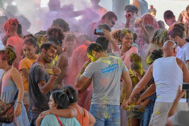 Un groupe de personnes se jette des poudres de couleurs pendant la Holi